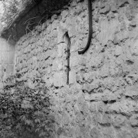 Vue partielle du mur nord de la nef unique romane, avec une fenêtre à linteau échancré, depuis le nord-ouest (1970)